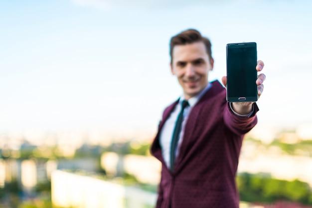 Jovem empresário sério de terno vermelho e camisa com gravata fica no telhado e mostra o telefone vazio