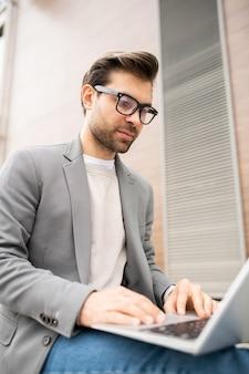 Jovem empresário sério em smart casual se concentrando em trabalhar em um novo projeto na frente de um laptop ao ar livre