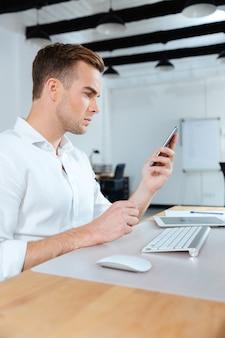 Jovem empresário sério sentado no local de trabalho e usando o telefone celular