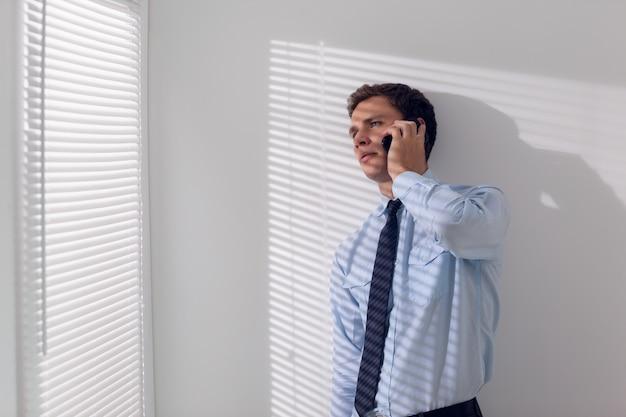 Jovem empresário sério usando o telefone móvel
