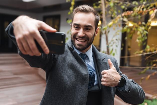 Jovem empresário sorridente atraente vestindo terno caminhando ao ar livre, tirando uma selfie