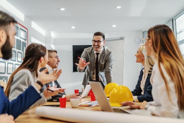 Jovem empresário sorridente caucasiano positivo tendo apresentação na sala de reuniões. seus colegas ouvindo e fazendo perguntas.
