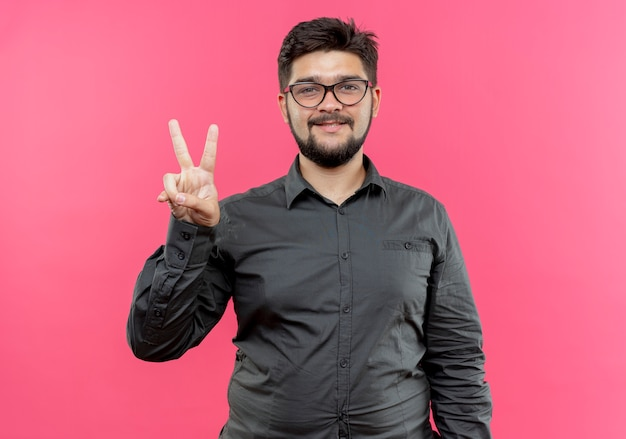 Jovem empresário sorridente de óculos mostrando um gesto de paz isolado em rosa