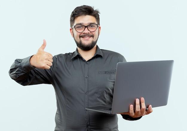 Jovem empresário sorridente de óculos, segurando o laptop com o polegar isolado no branco