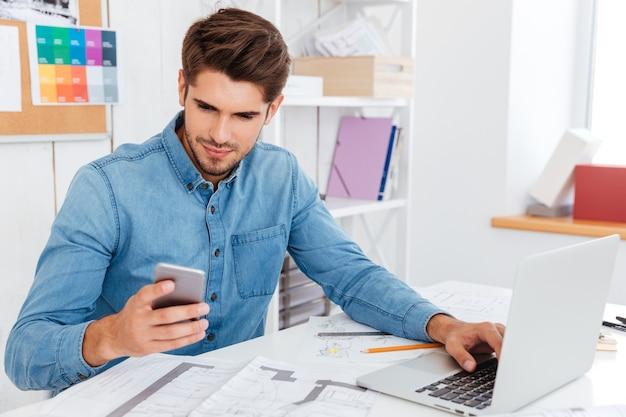Jovem empresário sorridente de óculos usando laptop e smartphone no local de trabalho