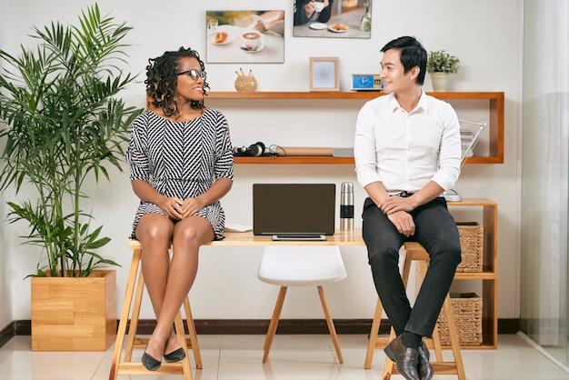 Jovem empresário sorridente e mulher de negócios sentados nas bordas da mesa de escritório, olhando um para o outro