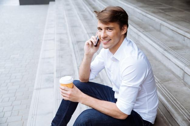 Jovem empresário sorridente em pé perto do centro de negócios e bebendo café