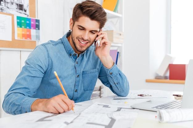 Jovem empresário sorridente, falando no celular e fazendo anotações enquanto está sentado no escritório