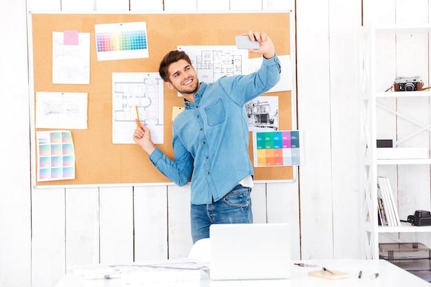 Jovem empresário sorridente fazendo selfie em frente ao quadro de tarefas no escritório