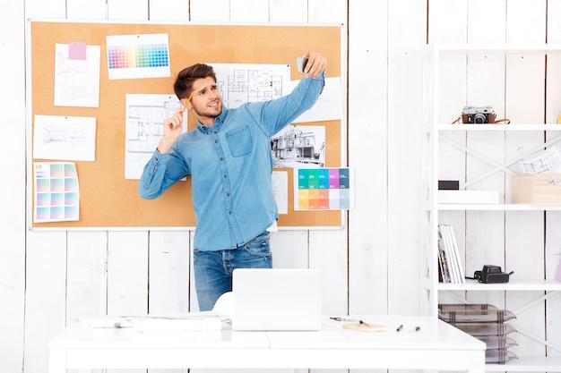 Jovem empresário sorridente fazendo selfie em frente ao quadro do escritório