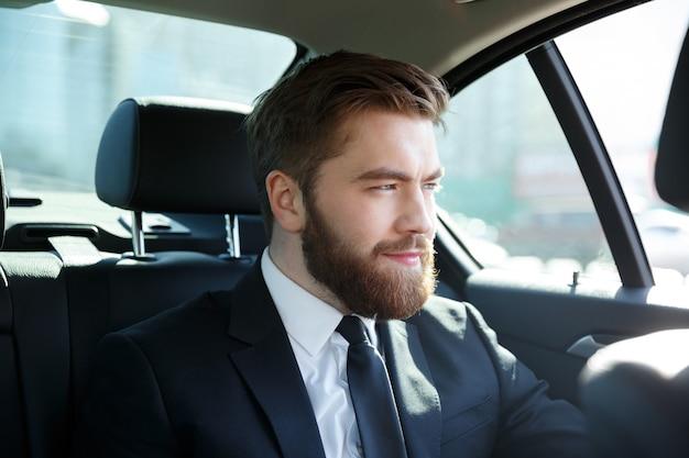 Jovem empresário sorridente, sentado em um carro