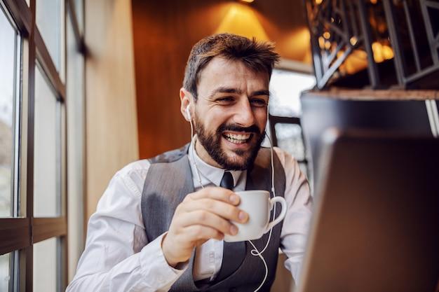 Jovem empresário sorridente, sentado na cafeteria ao lado da janela, segurando a xícara de café e tendo a videochamada com o colega.