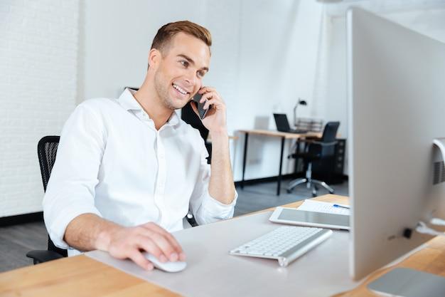 Jovem empresário sorridente, trabalhando com computador e falando ao celular no local de trabalho