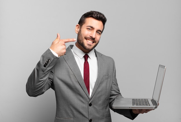 Jovem empresário sorrindo com confiança apontando para o próprio sorriso largo, atitude positiva, relaxada e satisfeita e segurando um laptop
