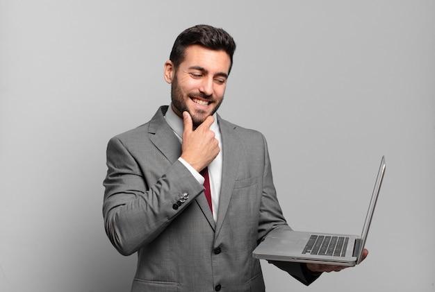 Jovem empresário sorrindo com uma expressão feliz e confiante com a mão no queixo, pensando e olhando para o lado e segurando um laptop