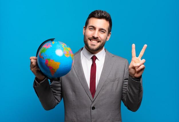 Jovem empresário sorrindo e parecendo amigável, mostrando o número dois ou o segundo com a mão para a frente, em contagem regressiva segurando um mapa do globo terrestre