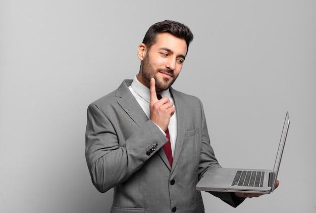 Jovem empresário sorrindo feliz e sonhando acordado ou duvidando, olhando para o lado e segurando um laptop