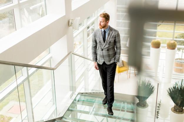 Jovem empresário subindo as escadas no prédio de escritórios