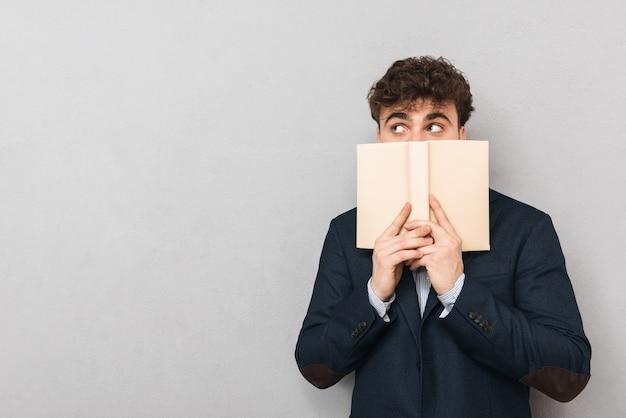 Jovem empresário surpreso de terno isolado sobre cinza, cobrindo o rosto com um livro