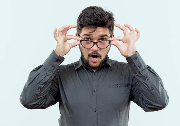 Jovem empresário surpreso usando óculos, agarrou óculos isolados no branco