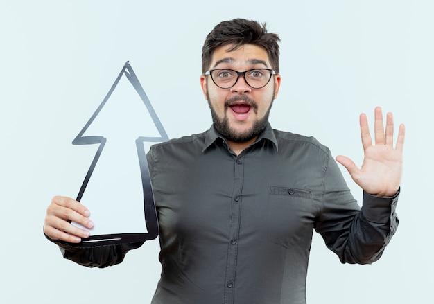 Jovem empresário surpreso usando óculos, segurando uma marca de direção e mostrando um gesto de parada isolado no branco