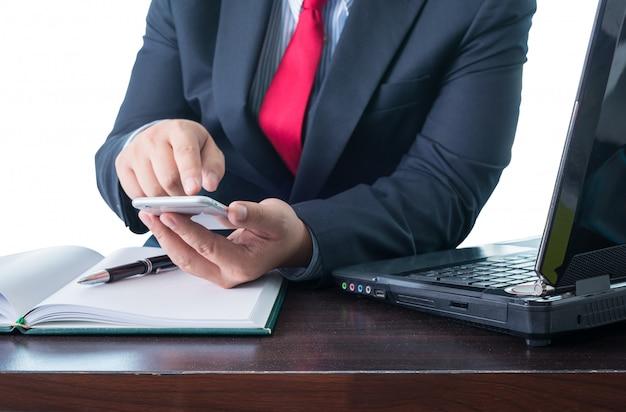 Jovem empresário trabalhando com dispositivos modernos, smartphone e computador portátil