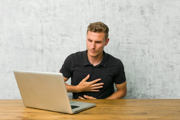 Jovem empresário trabalhando com seu laptop em uma mesa doente, sofrendo de dor de estômago, conceito de doença dolorosa.