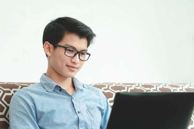 Jovem empresário, trabalhando felizmente com o laptop em casa.