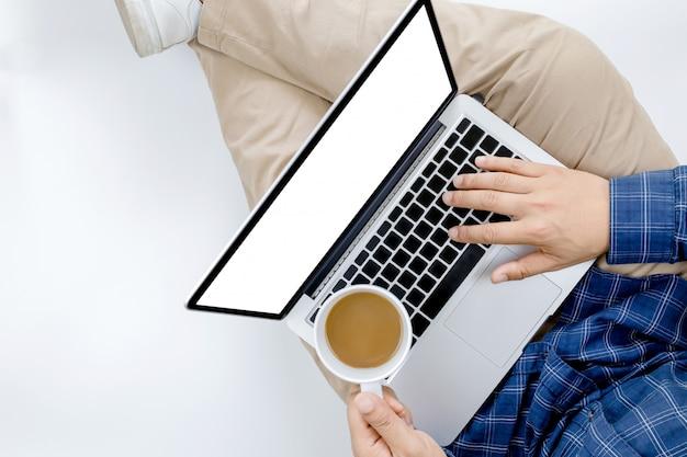 Jovem empresário trabalhando no computador portátil com café quente na mão