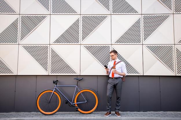Jovem empresário tranquilo usando smartphone e tomando um café no intervalo enquanto encosta na parede do centro de negócios contemporâneo