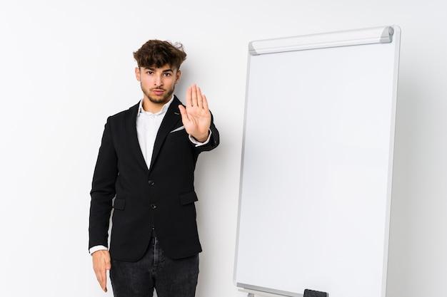 Jovem empresário, treinador árabe, em pé com a mão estendida, mostrando o sinal de pare, impedindo-o.