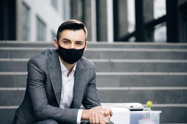 Jovem empresário triste com máscara médica sentado na escada perto de prédio comercial