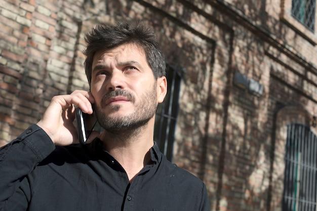 Jovem empresário urbano em smartphone na rua falando no smartphone