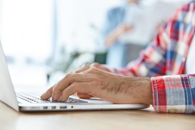Jovem empresário usa laptop moderno na mesa do escritório, digita informações e prepara relatório financeiro