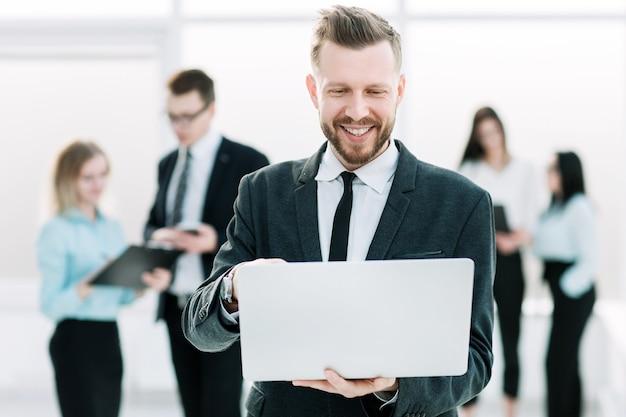 Jovem empresário usa um laptop em pé no corredor do escritório.