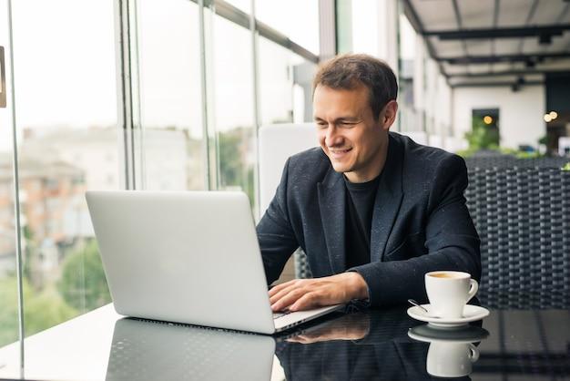 Jovem empresário usando laptop em um café
