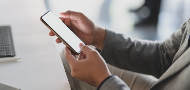 Jovem empresário usando smartphone de tela em branco