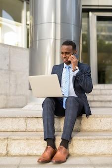 Jovem empresário usando telefone e laptop enquanto trabalha ao ar livre