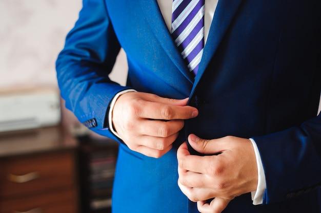 Jovem empresário veste um terno antes de encontrar os parceiros.