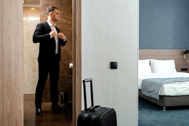 Jovem empresário viajante de camisa branca em pé em frente ao espelho e se vestindo para a reunião ou trabalho após chegar ao quarto do hotel com sua bagagem