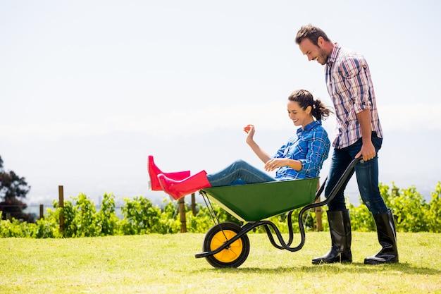 Jovem empurrando mulher sentada no carrinho de mão