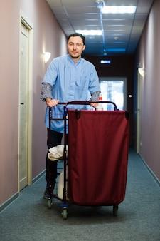 Jovem empurrando um carrinho de limpeza carregado com toalhas limpas, lavanderia e equipamentos de limpeza em um hotel, enquanto ele atende os quartos