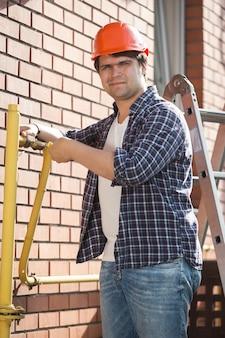 Jovem encanador com capacete de segurança fazendo manutenção de canos de gás amarelos fora de casa