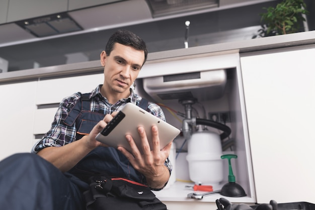 Jovem encanador senta-se perto do dissipador com tablet.
