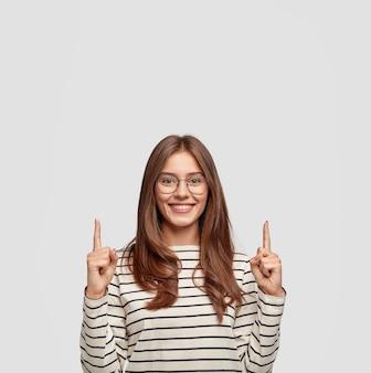 Jovem encantada com óculos posando contra a parede branca