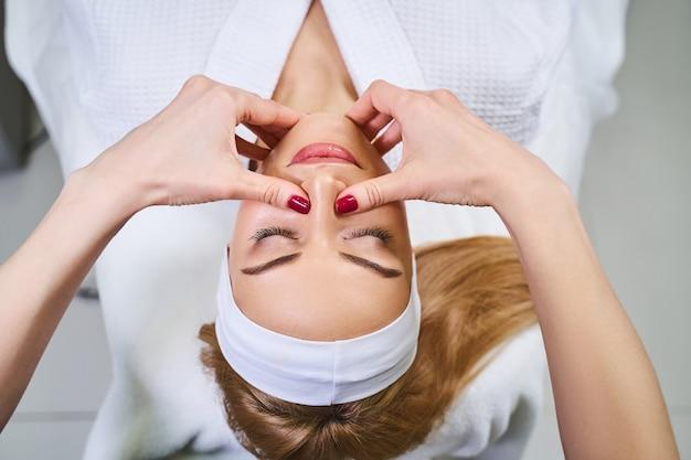 Jovem encantada está fechando os olhos e curtindo a massagem facial e manual para prevenir as rugas por profissional