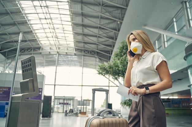 Jovem encantada falando ao telefone enquanto espera seu colega para uma viagem de negócios