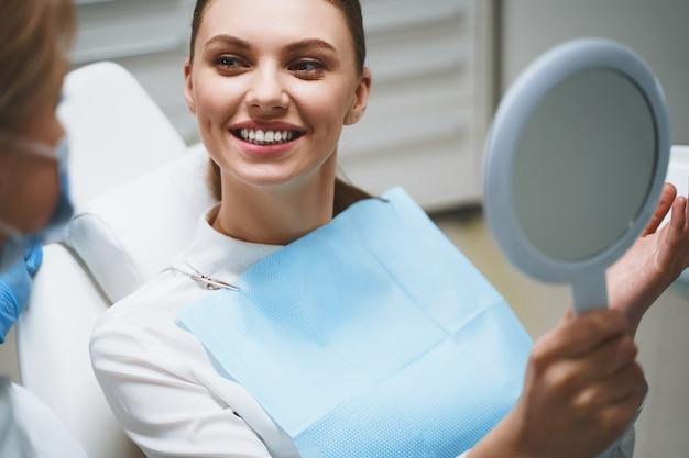 Jovem encantada na cadeira odontológica está conversando com o médico após o tratamento e se olhando no espelho