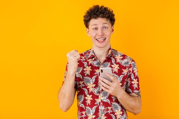 Jovem encantado usando celular e fazendo gesto de vencedor isolado em amarelo