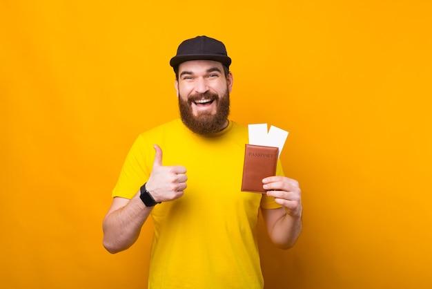 Jovem encantador com barba está pronto para as férias e segurando passaporte com ingressos
